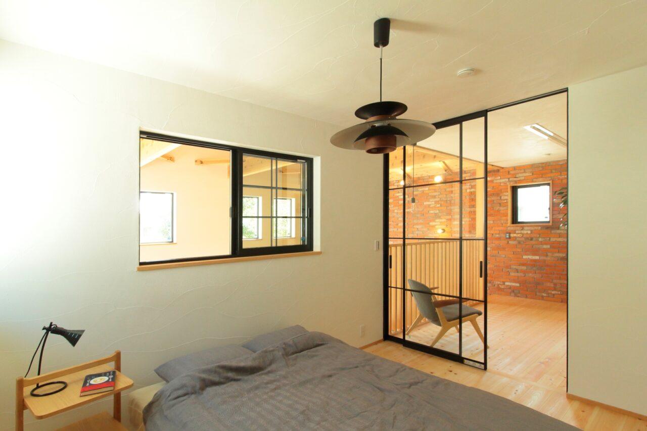 天井高まであるハイドアで仕切られた開放的な寝室