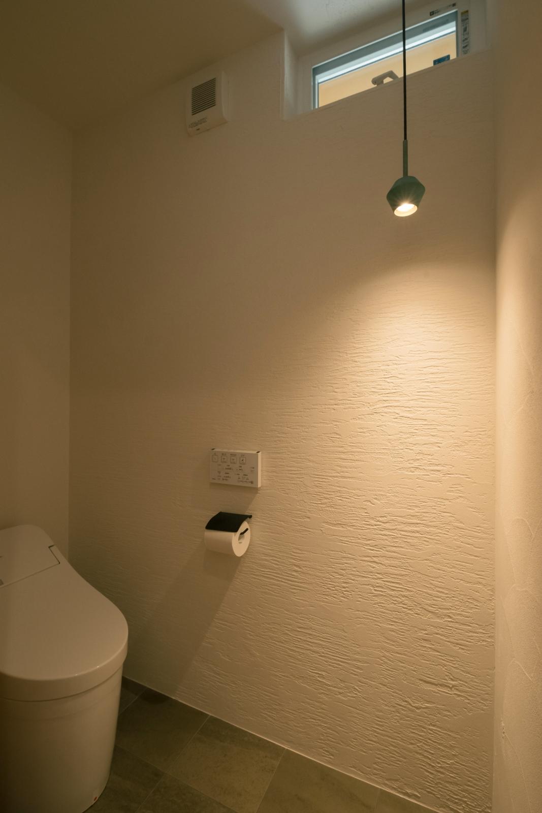 雰囲気のある照明と漆喰壁のトイレ